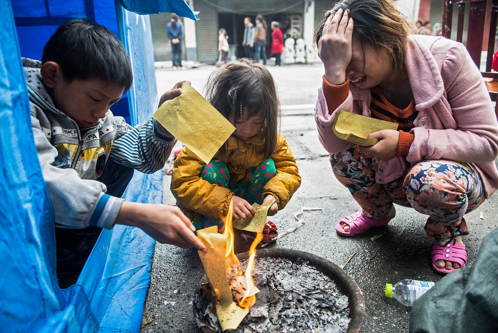. This photo taken on April 24, 2013 shows the wife (R) and children of Huang Zongxue, who died in an earthquake in Ya\'an, in southwest China\'s Sichuan province. The April 20 earthquake killed at least 193 people and injured more than 12,000, and left tens of thousands of homeless survivors living in makeshift tents or on the streets, facing shortages of food and supplies.  AFP/Getty Images