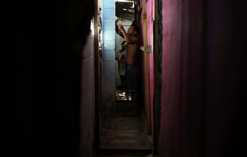 . A man from Brazil\'s Movimento dos Sem-Teto (Roofless Movement) fixes his shack at an area that used to be a nursery and school in Sao Paulo March 10, 2013. More than 1,200 people from Brazil\'s roofless movement live in an explosion prone area that has been contaminated with methane since October 2012, local media reported. According to the Environmental Sanitation Technology Company in the State of Sao Paulo (CETESB) the soil and water from the groundwater are contaminated with methane. Picture taken March 10, 2013. REUTERS/Nacho Doce