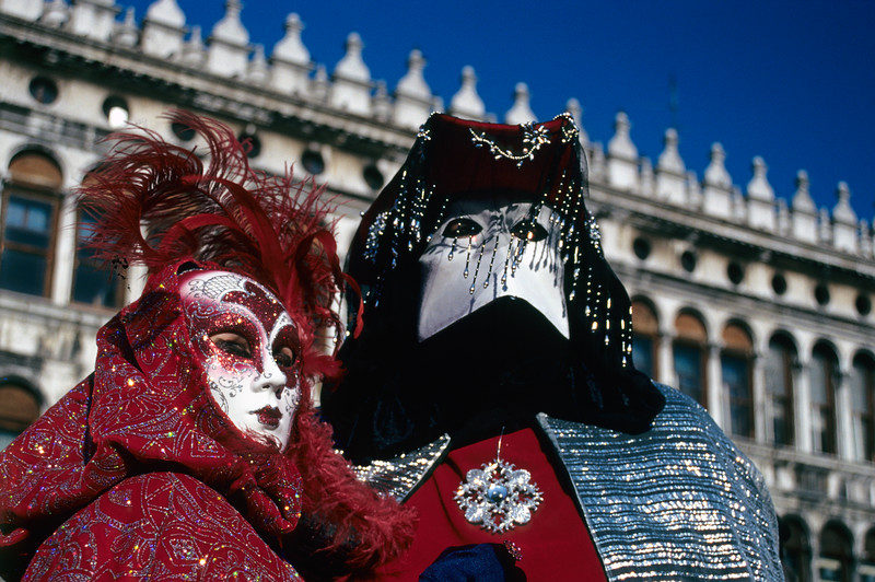 Two Persons Wearing Carnival Masks in front of Procuratie Vecchie Building at Piazza San Marco in Venice, Italy
