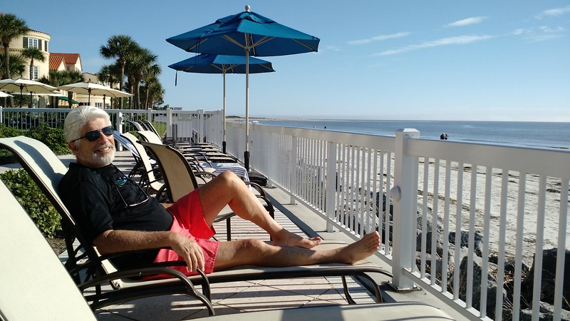 Man sits on a chaise overlooking the beach at St. Simons Island.