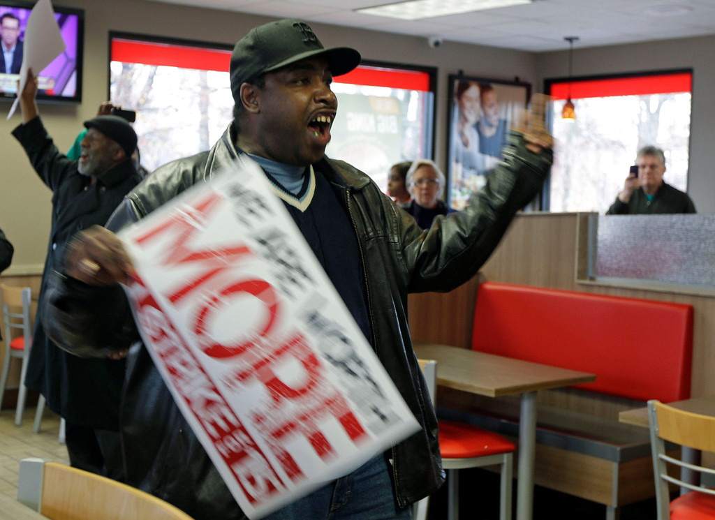 . Tremaine Tribble, of Charlotte, N.C., leads a chant inside a Burger King restaurant during a protest for a raise in the minimum wage in Charlotte, N.C., Thursday, Dec. 5, 2013. (AP Photo/Chuck Burton)