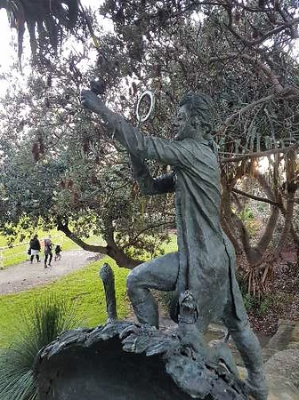Sculpture of Joseph Banks looking through magnifying glass at something in his left hand. Joe's on his own Sunday Adventure in Sydney.