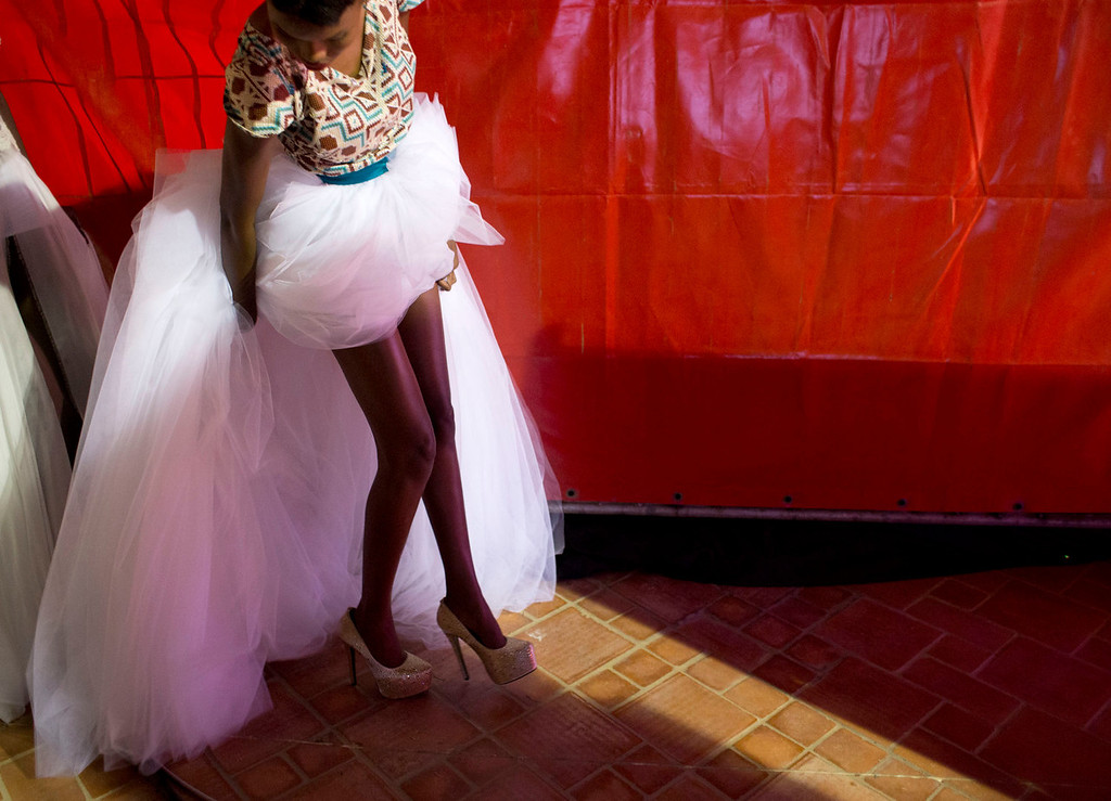 . A model wearing a creation by Elie Kuame of Lebanon and Ivory Coast arranges her skirt behind her as she prepares to walk the runway at Hotel des Almadies, in Dakar, Senegal, Saturday, June 22, 2013. After a Friday show held in a dusty marketplace in the working class suburb of Guediawaye, the runway finale of Dakar Fashion Week was held at a luxury hotel and showcased the work of 14 designers from West Africa, Europe, South America, and the Caribbean.(AP Photo/Rebecca Blackwell)