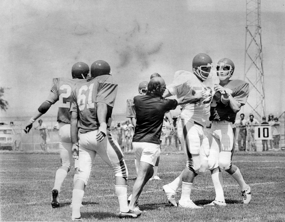 . July 17, 1976: Broncos equipment manager Larry Elliott, center, attempted to calm down Phil Olsen after he got into with Jim Cope in a scrimmage. (Duane Howell, The Denver Post)