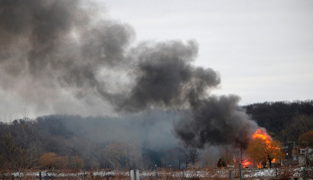 . Homes burn on Lake Road where two Webster firefighters were killed and two others were wounded after a gunman opened fire at a blaze in Webster, New York, December 24, 2012. A gunman shot dead two volunteer firefighters and injured two others when he ambushed them at the scene of an early morning house fire in a suburb of Rochester, New York, authorities said on Monday.   REUTERS/Max Schulte/Democrat and Chronicle/Handout