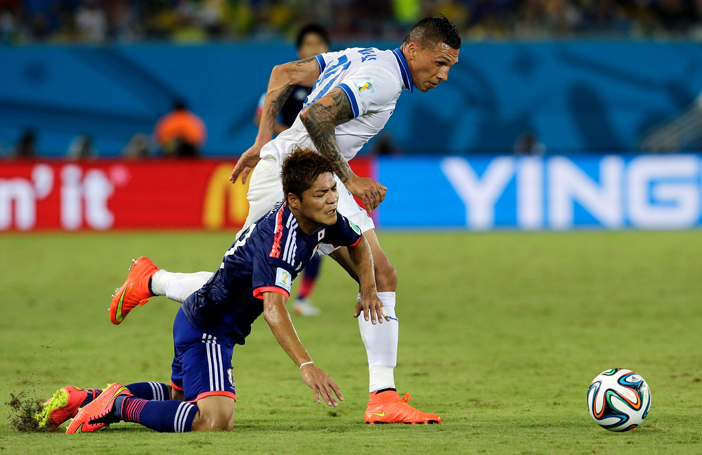 . Greece\'s Jose Holebas, right, pulls down Japan\'s Yoshito Okubo while chasing the ball during the group C World Cup soccer match between Japan and Greece at the Arena das Dunas in Natal, Brazil, Thursday, June 19, 2014.  (AP Photo/Shuji Kajiyama)
