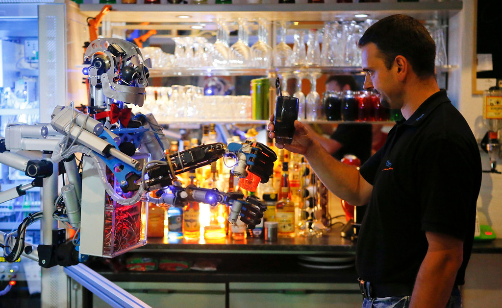 ". Mechatronics engineer Ben Schaefer (R) interacts with humanoid robot bartender ""Carl\"" as it prepares a drink for a guest at the Robots Bar and Lounge in the eastern German town of Ilmenau, July 26, 2013. The Humanoid robot bartender \""Carl\"", developed and built by Schaefer who runs a company for humanoid robots, prepares spirits for the mixing of cocktails and is able to interact with customers in small conversations. Picture taken July 26, 2013. REUTERS/Fabrizio Bensch"