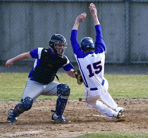 4/5/2017 Mike Orazzi | Staff Bristol Eastern's Gary Gagnier (11) tags out Plainville's Dwight Burns (15) at home plate Wednesday at Plainville High School.