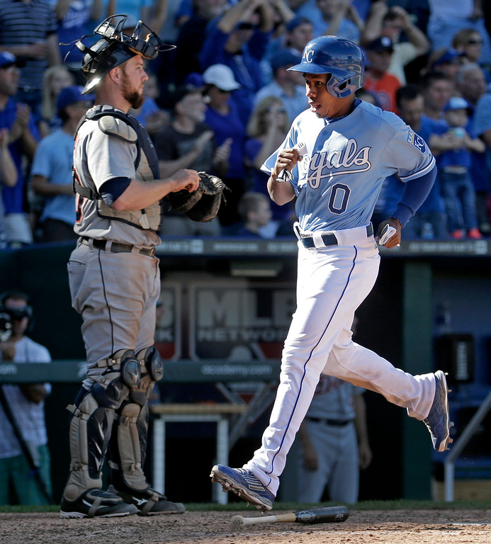 . Kansas City Royals\' Terrance Gore (0) runs past Detroit Tigers catcher Bryan Holaday to score on a double by Alex Gordon during the seventh inning of a baseball game Sunday, Sept. 21, 2014, in Kansas City, Mo. (AP Photo/Charlie Riedel)