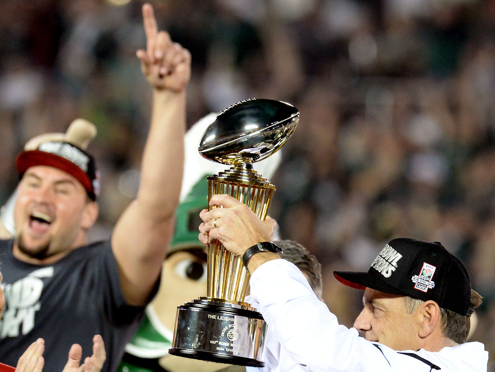 . Michigan State head coach Mark Dantonio holds-up the Leishman Trophy after defeating Stanford 24-20 during the 100th Rose bowl game in Pasadena, Calif., on Wednesday, Jan.1, 2014.   (Keith Birmingham Pasadena Star-News)