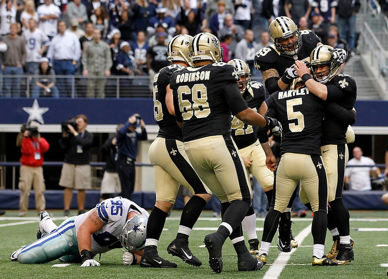 . New Orleans Saints quarterback Chase Daniel and guard Eric Olsen (69) embrace kicker Garrett Hartley (5) after Hartley kicked the game winning field goal against the Dallas Cowboys as defensive end Sean Lissemore (L) lays on the ground during overtime of their NFL football game in Arlington, Texas December 23, 2012.  REUTERS/Mike Stone