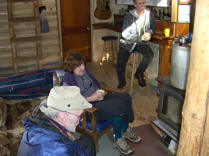 Warming up at the wood-burning stove.  Neal in the back.