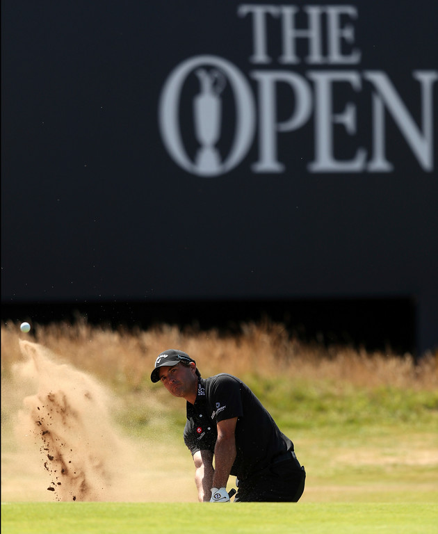 . Kevin Kisner of the US chips out of a bunker on the 18th hole during the first round of the British Open Golf Championship in Carnoustie, Scotland, Thursday July 19, 2018. (AP Photo/Jon Super)