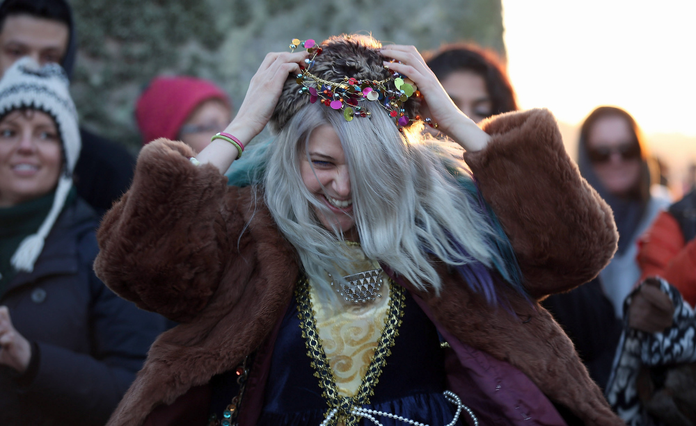 Description of . People dance as the sun rises, as druids, pagans and revellers, celebrate the winter solstice at Stonehenge on December 21, 2012 in Wiltshire, England. Predictions that the world will end today as it marks the end of a 5,125-year-long cycle in the ancient Maya calendar, encouraged a larger than normal crowd to gather at the famous historic stone circle to celebrate the sunrise closest to the Winter Solstice, the shortest day of the year.  (Photo by Matt Cardy/Getty Images)