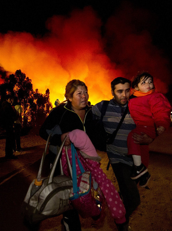 . Locals flee to safety after the fire reactivated in Valparaiso, Chile, on April 13, 2014.  More than 10,000 people were evacuated as an army of firefighters battled a killer blaze that --on the eve-- tore through parts of Chile\'s historic port of Valparaiso and left at least 11 people dead. The fire, which started in woodland Saturday, gutted 500 homes as flames advanced on the city of 270,000, famed for its UNESCO-listed center with cobblestone streets and brightly painted wooden homes. AFP PHOTO/MARTIN BERNETTI