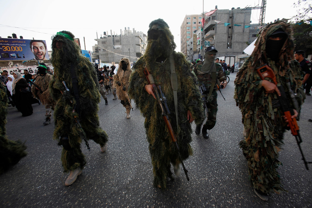 . Masked Palestinian members of the Ezz Al-Din Al Qassam brigade, the military wing of Hamas, in camouflage uniforms march with their weapons during a parade to mark the anniversary of a battle against Israel in Gaza City, Thursday, Nov. 14, 2013.  (AP Photo/Adel Hana)