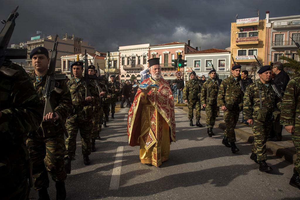 . An Orthodox priest holds a cross as he is accompanied by a guard of honour during an Epiphany ceremony to bless the water in Mytilene port on the northeastern Greek island of Lesbos, Wednesday, Jan. 6, 2016. Similar ceremonies to mark Epiphany Day were held across Greece at the sea, rivers, lakes and dams. An Orthodox priest throws a cross into the water and the swimmers race to retrieve it first. (AP Photo/Santi Palacios)
