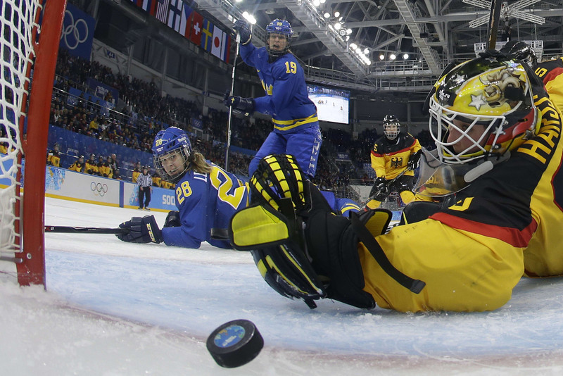 . Sweden\'s Michelle Lowenhielm (L) scores against Germany\'s goalkeeper Jennifer Harss during the Women\'s Ice Hockey Group B match Germany vs Sweden at the Shayba Arena during the Sochi Winter Olympics on February 11, 2014. Sweden won 0-4.  (MARK BLINCH/AFP/Getty Images)