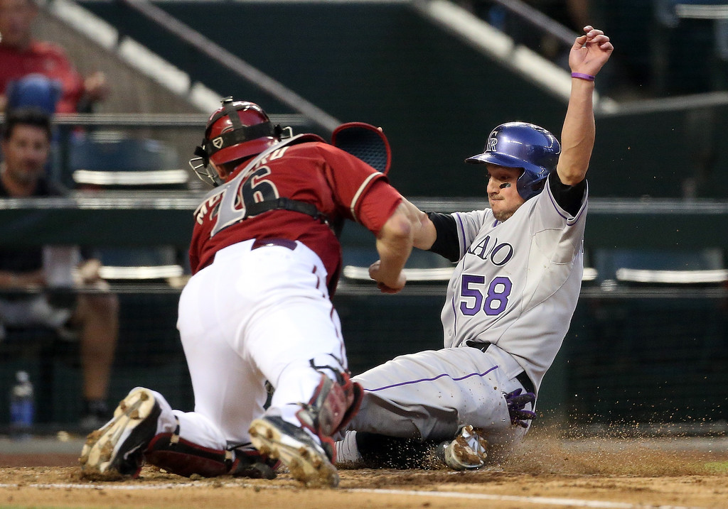 . Jordan Pacheco #58 of the Colorado Rockies is tagged out at home plate by catcher Miguel Montero #26 of the Arizona Diamondbacks as he attempts to score a run during the second inning of the MLB game at Chase Field on April 30, 2014 in Phoenix, Arizona.  (Photo by Christian Petersen/Getty Images)