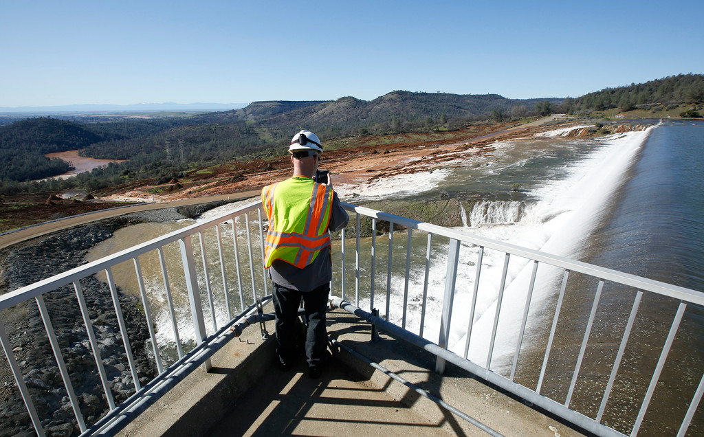 . Jason Newton, of the Department of Water Resources, takes a picture of water going over the emergency spillway at Oroville Dam Saturday, Feb. 11, 2017, in Oroville, Calif. Water started flowing over the emergency spillway, at the nation\'s tallest dam, for the first time Saturday morning after erosion damaged the Northern California dam\'s main spillway.(AP Photo/Rich Pedroncelli)