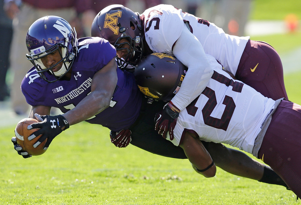 . Minnesota defensive back Brock Vereen (21) and linebacker Aaron Hill (57) tackle Northwestern wide receiver Christian Jones (14) during the first half of an NCAA college football game in Evanston, Ill., Saturday, Oct. 19, 2013. (AP Photo/Nam Y. Huh)