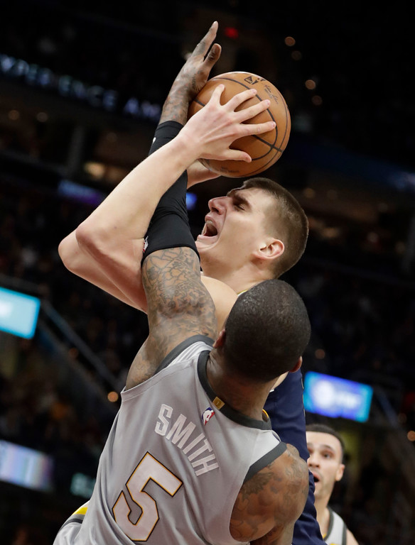 . Denver Nuggets\' Nikola Jokic, back, from Serbia, shoots against Cleveland Cavaliers\' JR Smith in the second half of an NBA basketball game, Saturday, March 3, 2018, in Cleveland. The Nuggets won 126-117. (AP Photo/Tony Dejak)