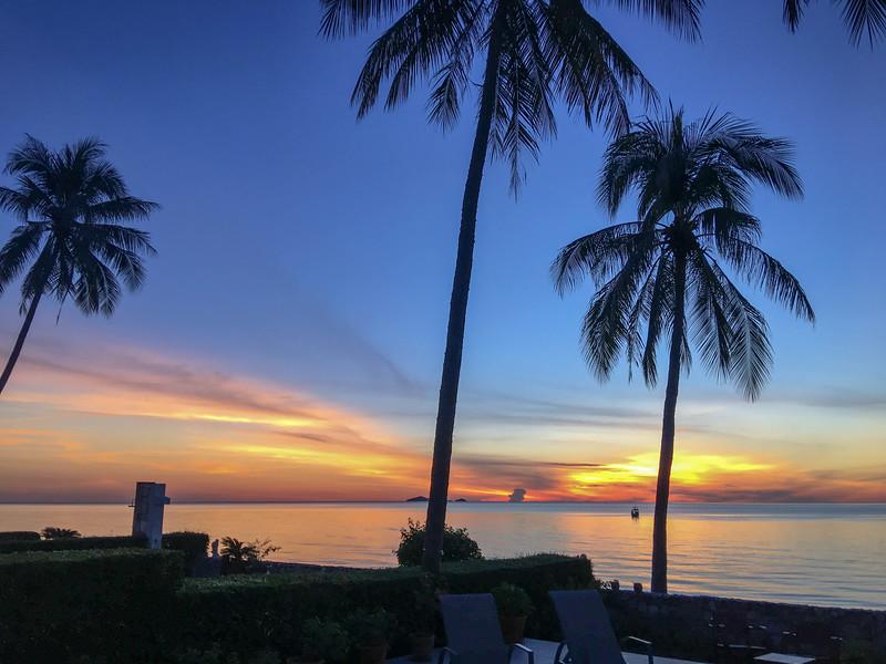 Blue sky tropical sunrise seascape with Palm trees, Thailand.
