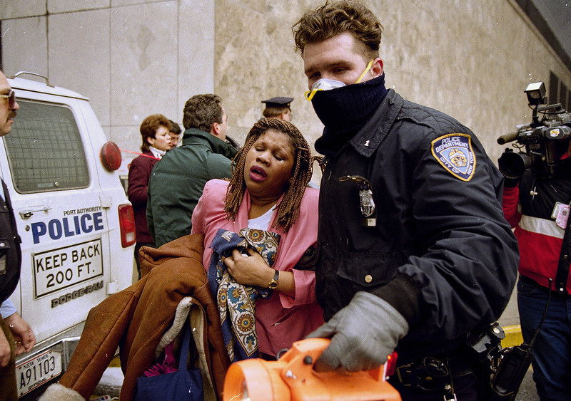 . A New York City police officer leads a woman to safety following an underground explosion at the World Trade Center on Feb. 26, 1993.  Hundreds were injured in the blast which caused the ceiling of a train station to collapse and set off fires below the twin towers.  (AP Photo/Alex Brandon)