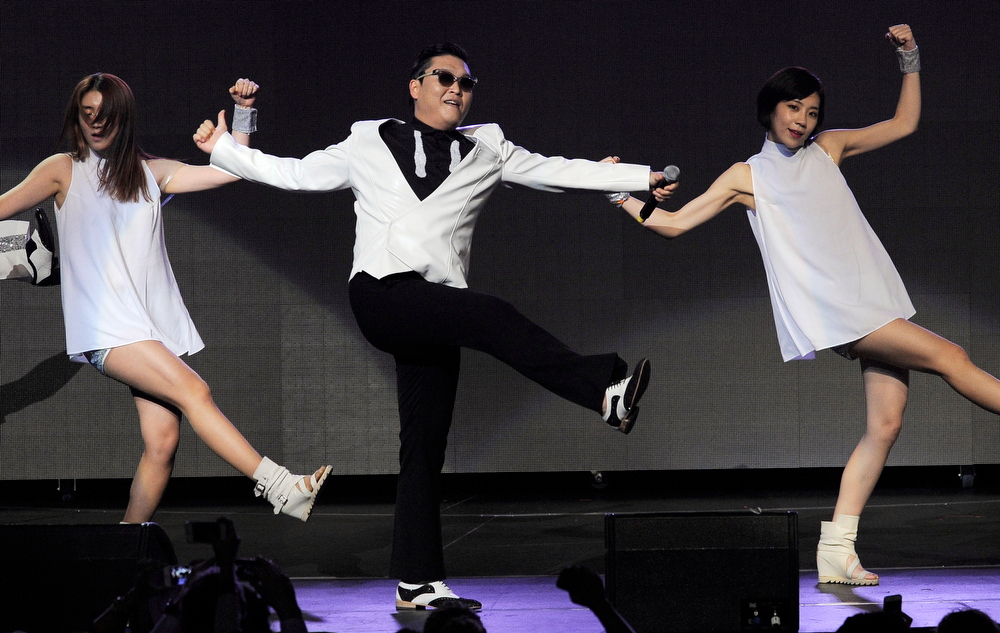 Description of . Psy, center, performs during the second night of KIIS FM's Jingle Ball at Nokia Theatre LA Live on Monday, Dec. 3, 2012, in Los Angeles. (Photo by Chris Pizzello/Invision/AP)