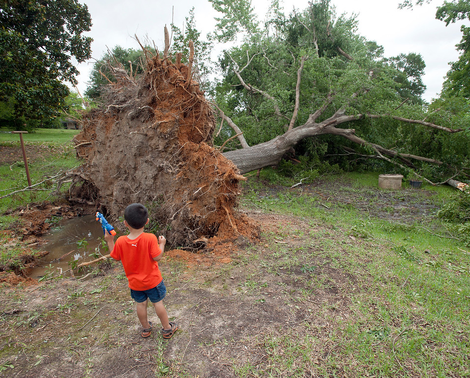 . Christopher Canales plays with a squirt gun outside of his home that was damaged by falling trees, Tuesday, May 26, 2015, in Henderson, Texas. A weekend of deadly and destructive storms caused widespread flooding in Texas. (Sarah A. Miller/The Tyler Morning Telegraph via AP)