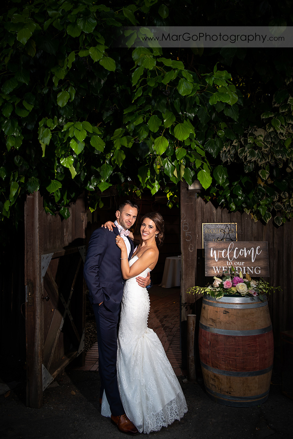 portrait of bride and groom in front of wood gate to wedding reception at San Pablo Rockefeller Lodge