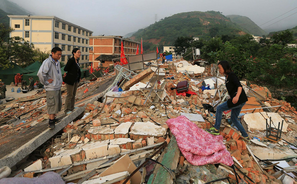 . In this photo provided by China\'s Xinhua News Agency, teachers search for their belongings from the collapsed dormitories at Longquan Middle School in Longtoushan town of Ludian county, southwest China\'s Yunnan Province, Tuesday, Aug. 5, 2014.  Ten-thousand Chinese soldiers are using pickaxes and backhoes in an ongoing effort to clear roads and dig residents from collapsed homes after Sunday\'s 6.1-magnitude earthquake in southwest China.   (AP Photo/Xinhua, Xing Guangli)