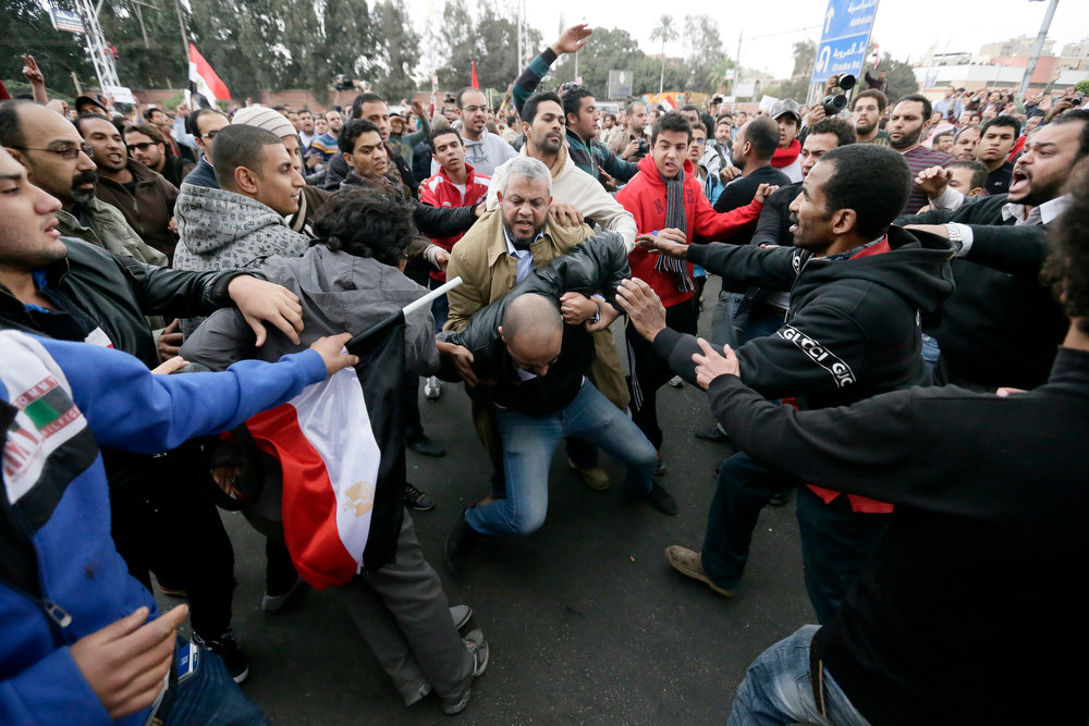 Description of . Egyptian President Mohammed Morsiís supporters beat an opponent, center, during clashes outside the presidential palace, in Cairo, Egypt, Wednesday, Dec. 5, 2012. Wednesdayís clashes began when thousands of Islamist supporters of Morsi descended on the area around the palace where some 300 of his opponents were staging a sit-in. (AP Photo/Hassan Ammar)