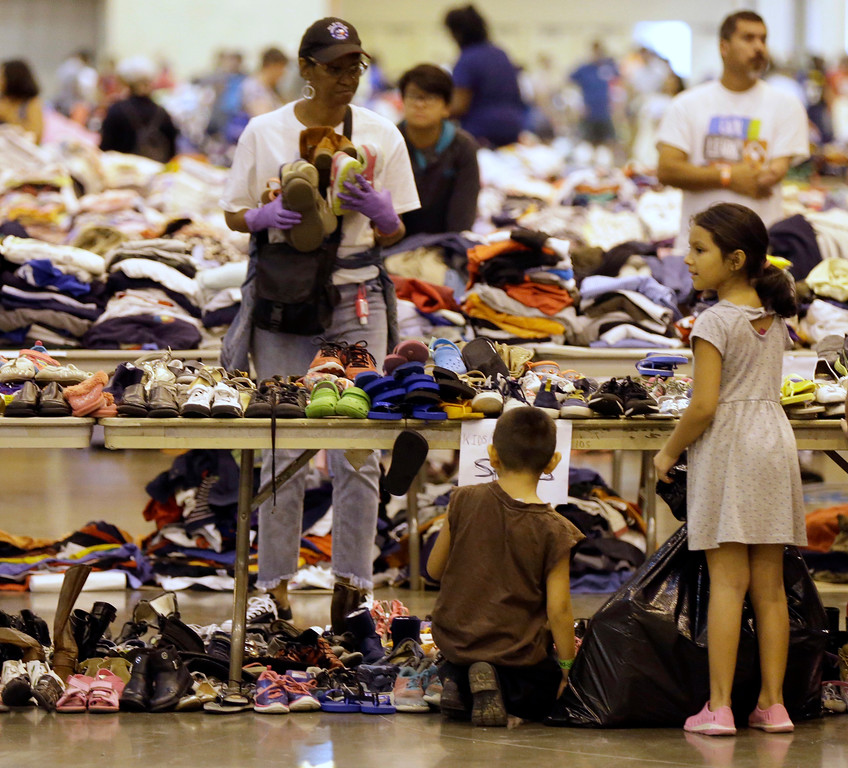 . Harvey flood evacuee children look through donated shoes at a shelter setup inside NRG Center Wednesday, Aug. 30, 2017, in Houston. (AP Photo/David J. Phillip)