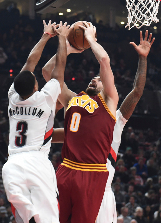 . Cleveland Cavaliers forward Kevin Love drives to the basket on Portland Trail Blazers guard C.J. McCollum during the first half of an NBA basketball game in Portland, Ore., Wednesday, Jan. 11, 2017. (AP Photo/Steve Dykes)