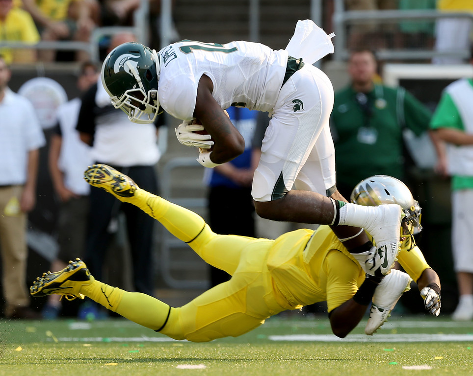 . Michigan State\'s Tony Lippett, top, goes up over the top of Oregon\'s Reggie Daniels for a gain in the 2nd quarter of their college football game in Eugene, Oregon, Saturday Sept. 6, 2014. (AP Photo/Chris Pietsch)
