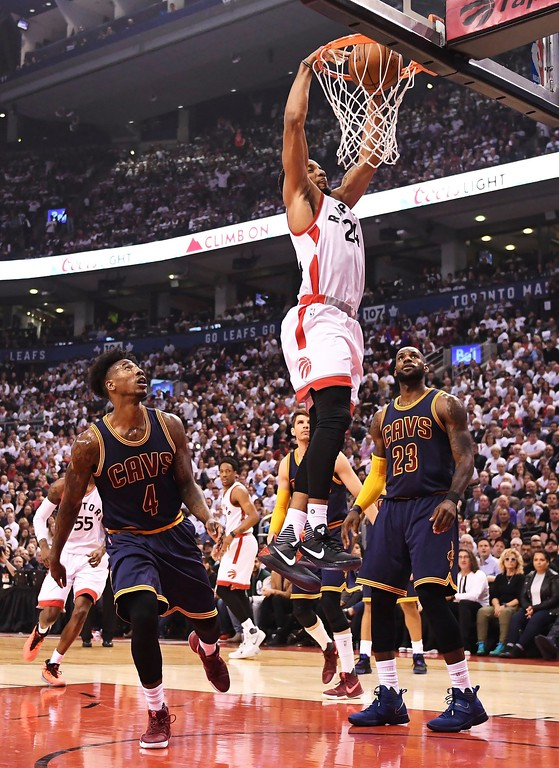 . Toronto Raptors guard Norman Powell (24) dunks as Cleveland Cavaliers guard Iman Shumpert (4) and forward LeBron James (23) look on during the first half of Game 3 of an NBA basketball second-round playoff series in Toronto on Friday, May 5, 2017. (Frank Gunn/The Canadian Press via AP)