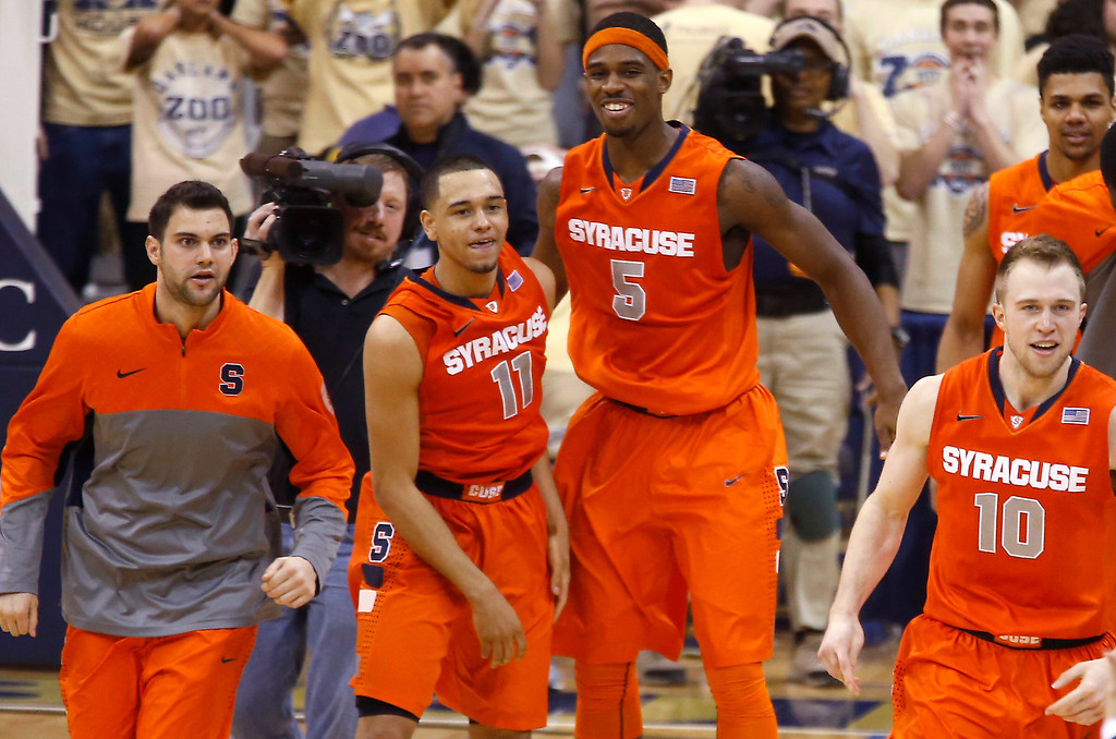 . Syracuse\'s Tyler Ennis (11) celebrates with teammate C.J. Fair (5) and others after hitting a 3-point shot with less than a second in the NCAA college basketball game against Pittsburgh on Wednesday, Feb. 12, 2014, in Pittsburgh. Syracuse won 58-56. (AP Photo/Keith Srakocic)