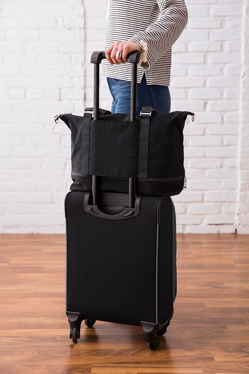 Example of how the expandable carry on bag fits over the handle of a rolling carryon.
