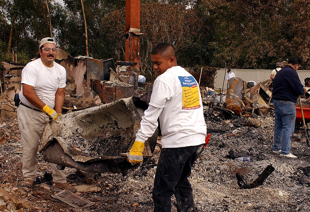 . Sergio Lopez, left, and Norberto Murillo, right,  carry away a bathtub as they help homeowner Donald Faye clear his lot for reconstruction Saturday, Nov. 1, 2003, in  the Scripps Ranch neighborhood of San Diego. When the western edge of the fast-moving Cedar Fire entered San Diego on Oct. 26, it destroyed Faye\'s house and more than 300 others in the  bedroom community of 30,000 people. (AP Photo/Denis Poroy)