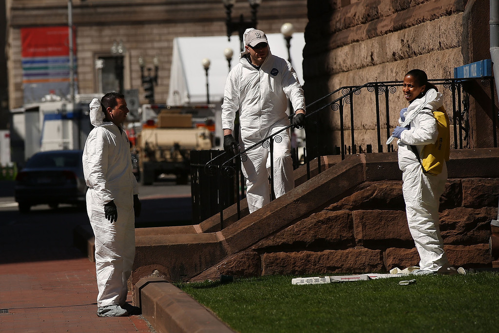 . Members of the Federal Bureau of Investigation (FBI) search for clues near the scene of twin bombings at the Boston Marathon on April 17, 2013 in Boston, Massachusetts. The explosions, which occurred near the finish line of the 116-year-old Boston race on April 15, resulted in the deaths of three people with more than 170 others injured. Security has been heightened across the nation as the search continues for the person or people behind the bombings.  (Photo by Spencer Platt/Getty Images)