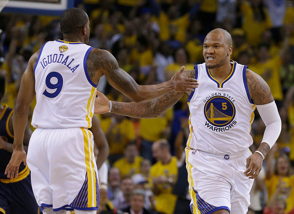 . Golden State Warriors forward Andre Iguodala (9) reacts with forward Marreese Speights (5) during the first half of Game 1 of basketball\'s NBA Finals against the Cleveland Cavaliers in Oakland, Calif., Thursday, June 4, 2015. (AP Photo/Ben Margot)