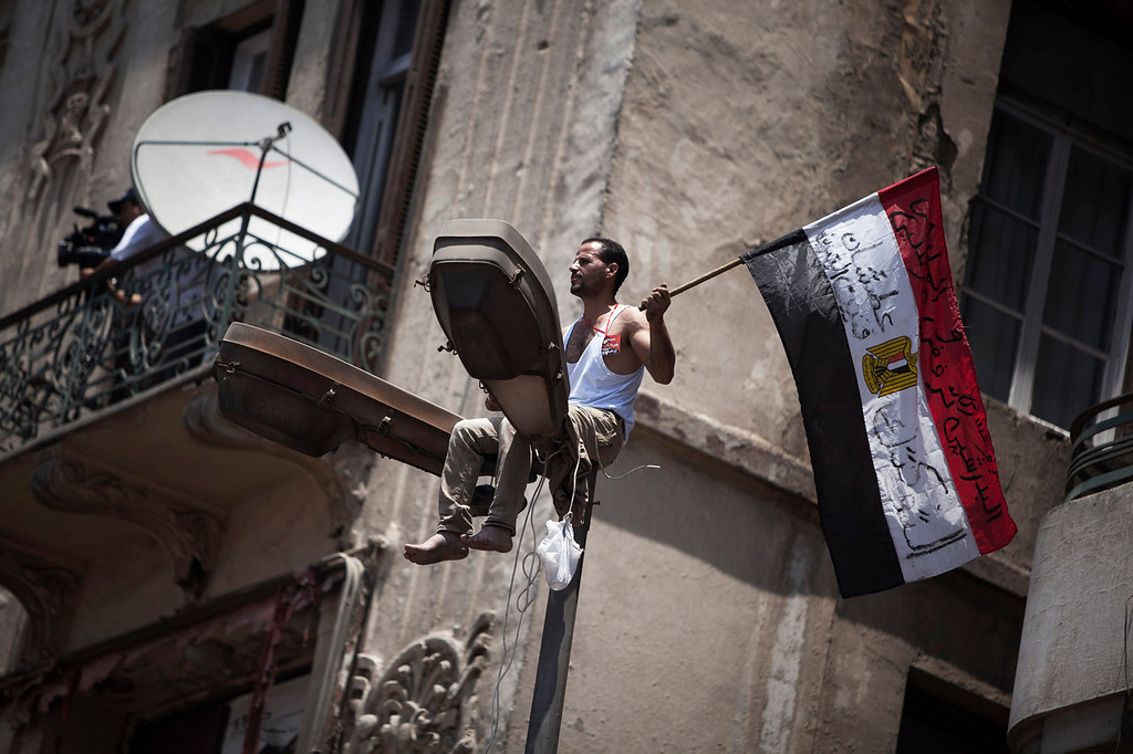 . An Egyptian protester waves a national flag from the top of a light pole during a demonstration against Egypt\'s Islamist President Mohammed Morsi in Tahrir Square in Cairo, Sunday, June 30, 2013. Thousands of opponents and supporters of Egypt\'s Islamist president began massing in city squares in competing rallies Sunday, gearing up for a day of massive nationwide protests that many fear could turn deadly as the opposition seeks to push out Mohammed Morsi. (AP Photo/ Manu Brabo)