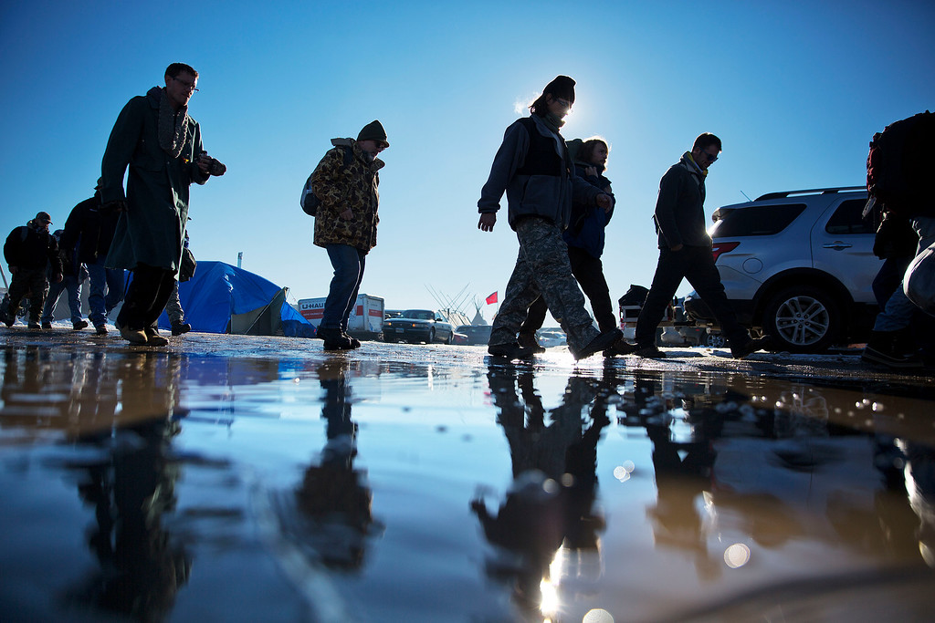 . Veterans walk to their sleeping quarters after arriving at the Oceti Sakowin camp where people have gathered to protest the Dakota Access oil pipeline in Cannon Ball, N.D., Sunday, Dec. 4, 2016. Tribal elders have asked the military veterans joining the large Dakota Access pipeline protest encampment not to have confrontations with law enforcement officials, an organizer with Veterans Stand for Standing Rock said Sunday, adding the group is there to help out those who\'ve dug in against the four-state, $3.8 billion project. (AP Photo/David Goldman)