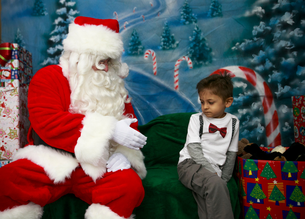 Description of . Therapist John Pettingill, dressed as Santa Claus, reaches out to Reece Gonzalez, 5, during the Sensitive Santa Program at Touchstone Behavioral Health in Mesa on Monday, Dec. 10, 2012.  Touchstone Behavioral Health brought its Sensitive Santa to Mesa on Monday and will make him available for free visits by autistic children.  To see Sensitive Santa, children aren't forced to wait in lines, and the environment is quiet and calm.  (AP Photo/The Arizona Republic, Charlie Leight)
