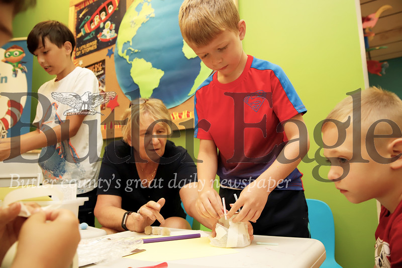 "Library volunteer Monica Rummel helps Emmett Eyler, 6, work on his lunar lander as part of a STEM program at the South Butler Library in Saxonburg. One of the stations involved building lander modules that would keep puff ball ""astronauts"" safe when dropped from the table to ""land."" 7/25/19 Seb Foltz/Butler Eagle"
