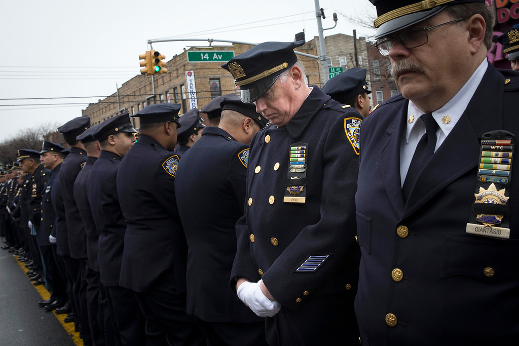 . Some police officers turn their backs as Mayor Bill de Blasio speaks during the funeral of New York Police Department Officer Wenjian Liu at Aievoli Funeral Home, Sunday, Jan. 4, 2015, in the Brooklyn borough of New York. Liu and his partner, officer Rafael Ramos, were killed Dec. 20 as they sat in their patrol car on a Brooklyn street. The shooter, Ismaaiyl Brinsley, later killed himself. (AP Photo/John Minchillo)