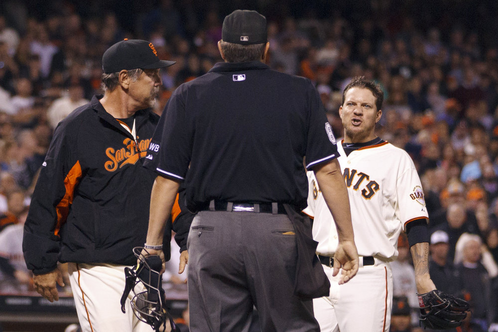. Jake Peavy #22 of the San Francisco Giants and manager Bruce Bochy #15 argue with umpire Doug Eddings #88 during the seventh inning against the Colorado Rockies at AT&T Park on August 25, 2014 in San Francisco, California.  (Photo by Jason O. Watson/Getty Images)