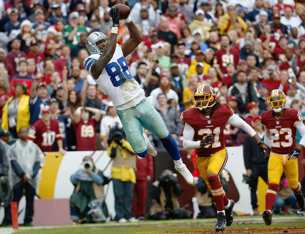 . Dallas Cowboys wide receiver Dez Bryant pulls in a touchdown pass next to Washington Redskins strong safety Brandon Meriweather during the first half of an NFL football game in Landover, Md., Sunday, Dec. 22, 2013. (AP Photo/Alex Brandon)
