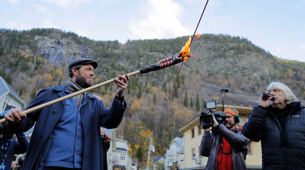 """. Artist Martin Andersen inaugurates the giant mirrors (\""""Solspeilet\"""") installed on the hillside above Rjukan, aimed to reflect sunlight down on the town square, on October 30, 2013, 100 years after the idea was first released. Andersen who arrived in the village from Paris, picked up the idea around ten years ago. Residents of a remote village nestled in a steep-sided valley in southern Norway are about to enjoy winter sunlight for the first time ever thanks to giant mirrors. AFP PHOTO / KRISTER SOERBOE/AFP/Getty Images"""